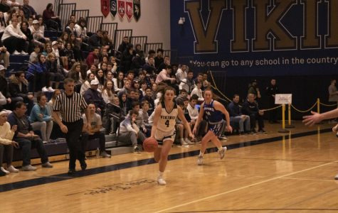 Point guard Lily Pulsifer rushing down the sideline  toward the basket.