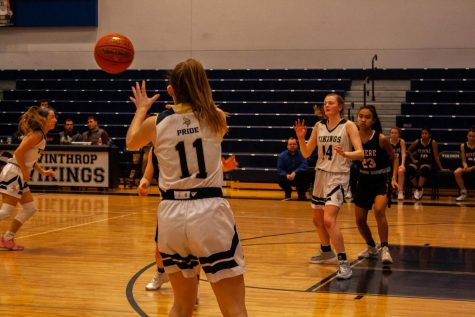 #11 Carolyn Kinsella catches a pass as she prepares to shoot a basket.